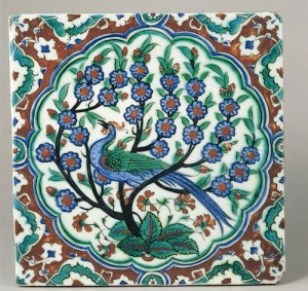 An Iznik pottery tile with peacock and flowering tree
