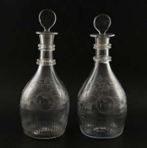 A pair of early 19th century Waterford mould blown bottle shaped decanters with stoppers (2)