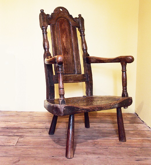 A large and important-looking chair, with a thick dished seat and low legs, and a tall and complex back in a vernacular version of the Carolean style. In a mixture of ash, sycamore and fruitwood, the surface has a natural shine through usage, with the reverse being completely raw. Pembrokeshire, c. 1710-1730. Author's collection