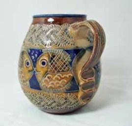 A salt-glaze jug made in the studios of Giefer-Bahn, Höhr-Grenzhausen (Rhine- land-Palatinate). The jug is decorated in sgraffito with an atmospheric retro fish design. Signed to the base. Circa 1960/70. From John Newton Antiques