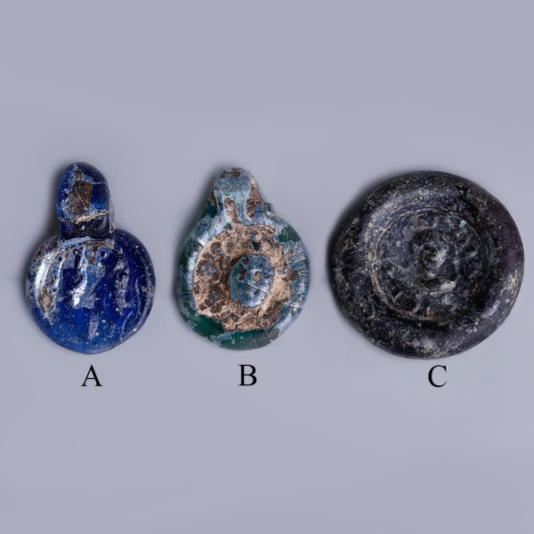 A Selection of Ancient Roman Glass Pendants and Disk with Stamped Ornaments