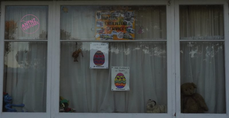 "A picture of a white window, with curtains shut. Behind the glass are several teddy bears on the window sill, a stuffed Kiwi hanging from the frame, two colored-in Easter eggs and one Poster with text saying ""Thanks essential workers"" surrounded by smaller pictures representing different essential services"