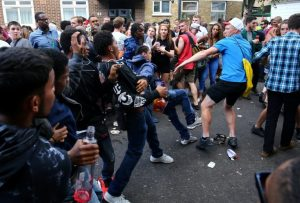 People fighting during the Notting Hill Carnival parade, London. The Notting Hill Carnival is the largest street festival in Europe and originated in 1964 as a way for Afro-Caribbean communities to celebrate their own cultures and traditions. 29 August 2016.