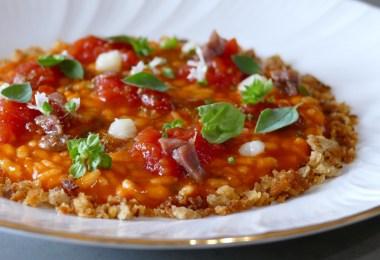 Un primo piatto estivo e fresco, colorato e profumato, che richiama la pizza alla marinara completa di acciughe. Un capolavoro.