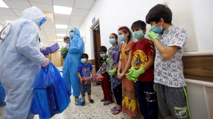 सुरक्षात्मक सूट और फेस मास्क पहनने वाले नर्स और स्वयंसेवक उन बच्चों को उपहार देते हैं जो कोविद -19 से संक्रमित थे और इराक के पवित्र शहर नजफ के एक अस्पताल में संगरोध वार्ड में भर्ती हुए थे। (फाइल फोटो: रॉयटर्स)
