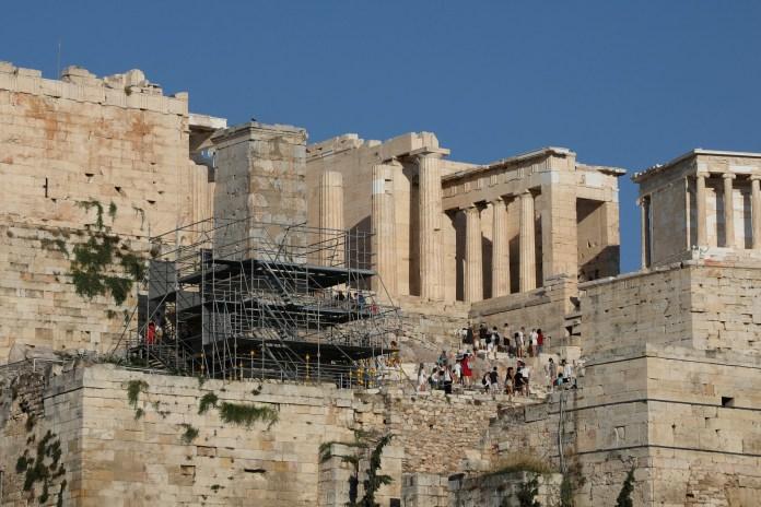 पर्यटक 25 जुलाई, 2021 को एथेंस, ग्रीस में एक्रोपोलिस के ऊपर प्रोपीलिया में अपना रास्ता बनाते हैं। चित्र 25 जुलाई, 2021 को लिया गया। REUTERS/Louiza Vradi
