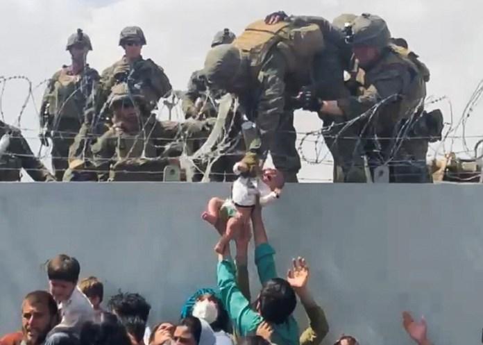 सोशल मीडिया से प्राप्त वीडियो से ली गई इस स्थिर छवि में, काबुल, अफगानिस्तान में, 19 अगस्त, 2021 को हवाई अड्डे की परिधि की दीवार पर एक बच्चे को खाली करने के लिए अमेरिकी सेना को सौंप दिया गया है।  वीडियो 19 अगस्त, 2021 को लिया गया। उमर हैदरी/रायटर के माध्यम से