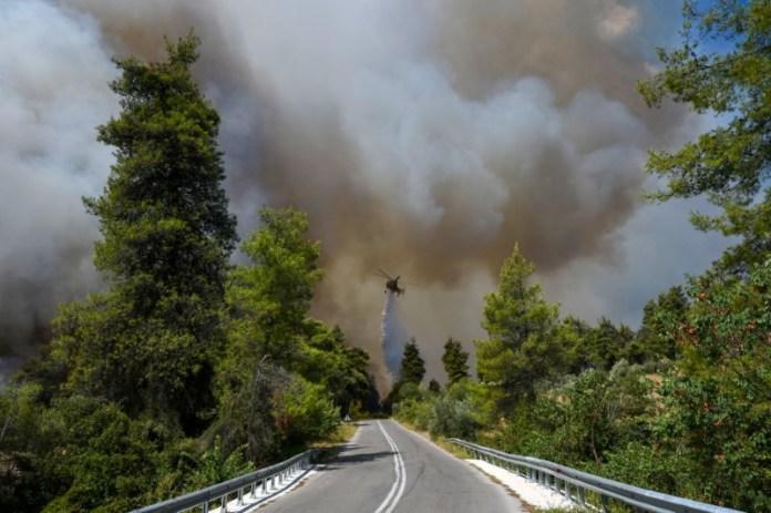 ८ अगस्त, २०२१ को ग्रीस के इविया द्वीप पर एल्लिनिका गांव के पास जंगल की आग जलती हुई आग बुझाने वाला हेलीकॉप्टर पानी की बूंद बनाता है।