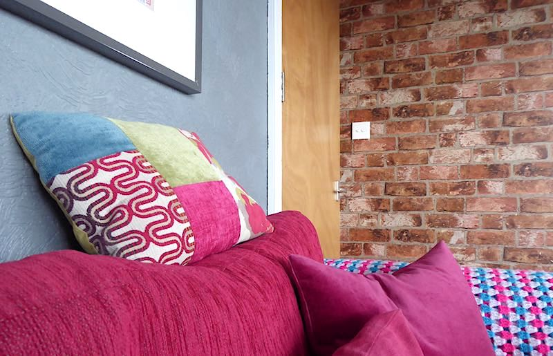 pink sofa and brick wall in high-rise
