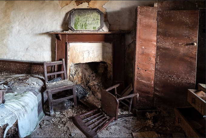 fireplace, bed and chairs in abandoned house