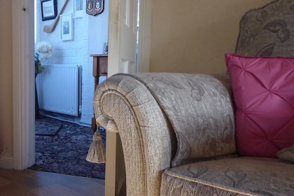 armchair with cushion and door to hall