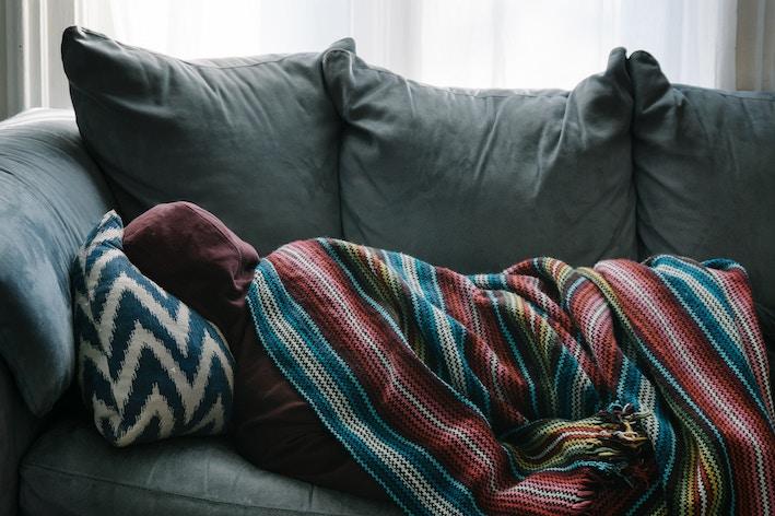 person sleeping on grey sofa