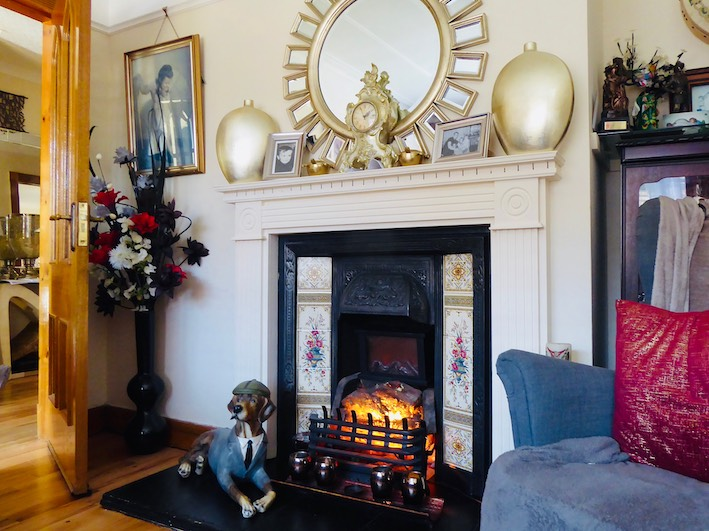 cream fireplace with gold mirror and ornamental dog