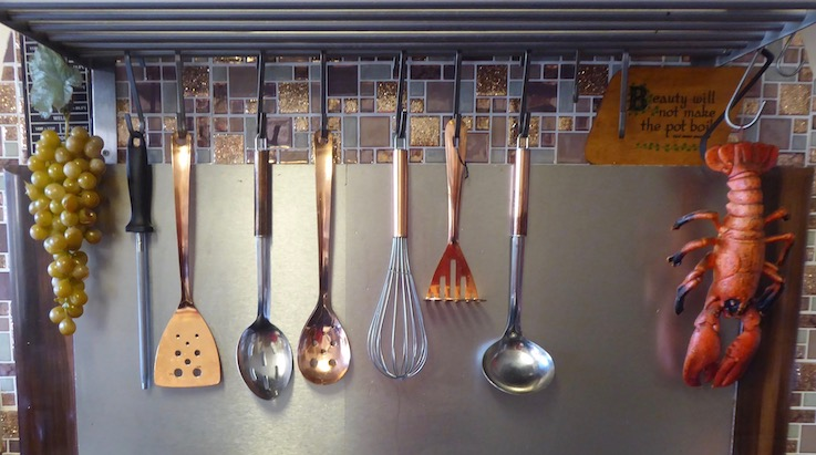 kitchen tools hanging above cooker