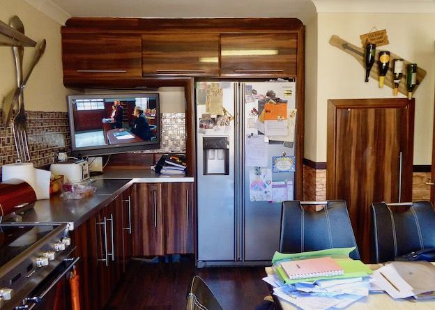 brown kitchen cupboards, fridge and TV