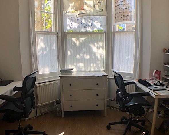 2 desks by large window