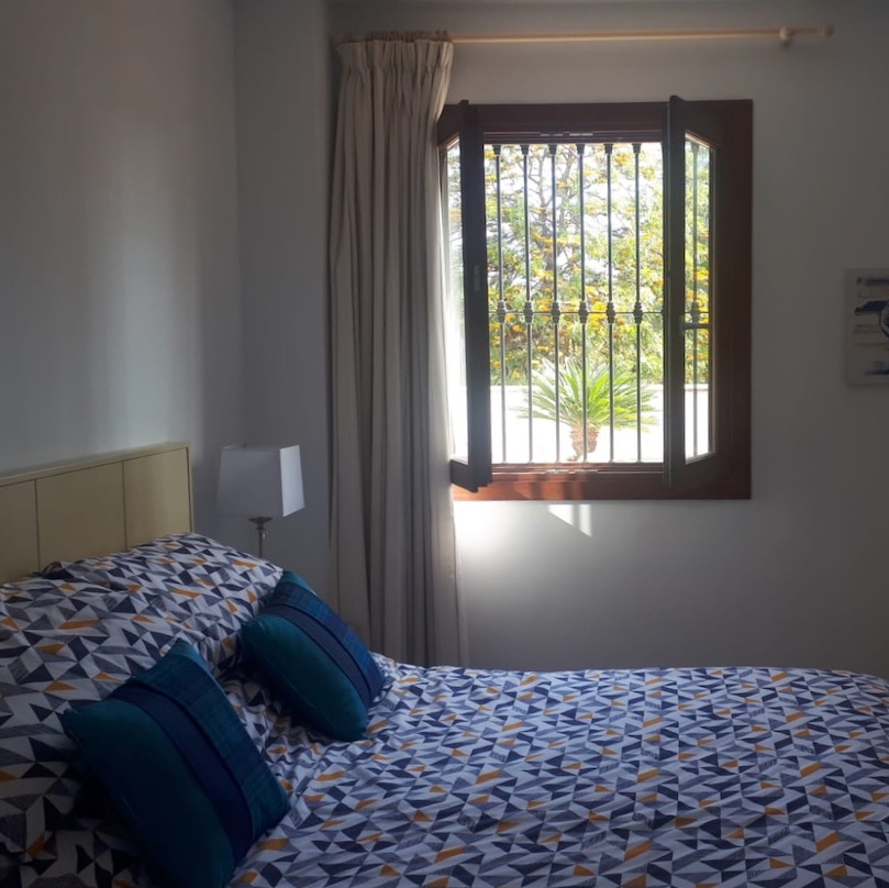 bed with clue quilt and window with bars Spain