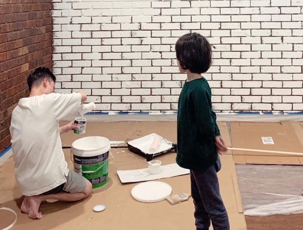 2 boys. One painting brick wall white