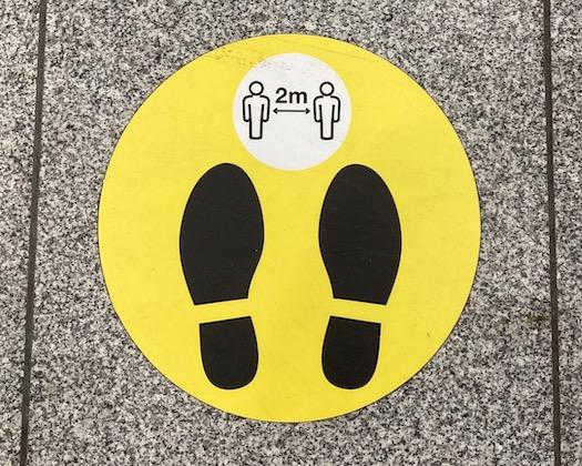 two feet Covid sign on floor