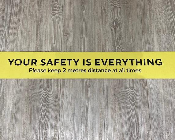 yellow Covid warning sign on floor