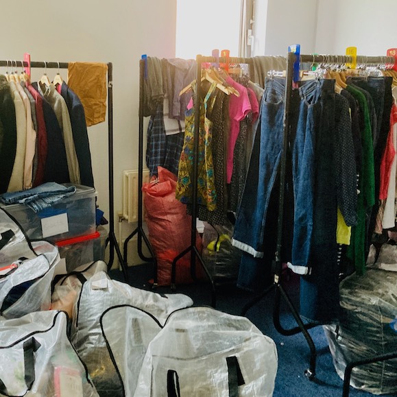 clothes in bags and railings to be sorted