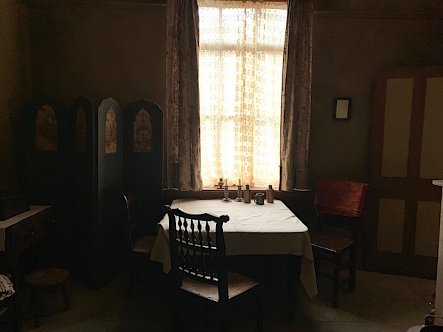 dark parlour with central window, table and chair