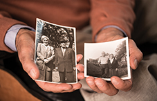 Dr. Ervin Staub holds a photo of his parents Rosza and Joszef Staub (left), and one of Maria Gogan (right) who helped his family in World War II.