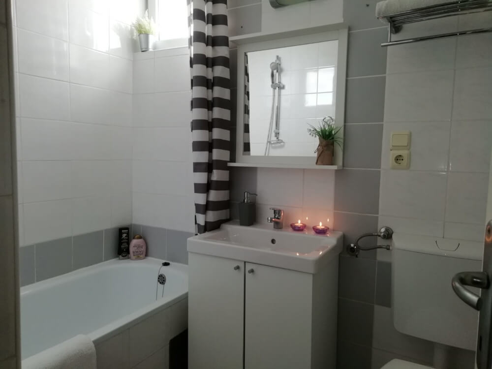 Bath tub, washbasin with two candles burning in Apartment 3 in Apartmani Smiljana in Primošten