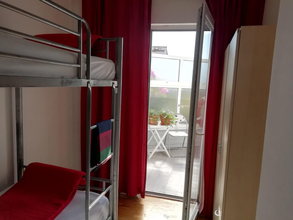 Bunk bed with red blanket, red curtains in room with open door to small balcony in Apartmani Smiljana in Primošten