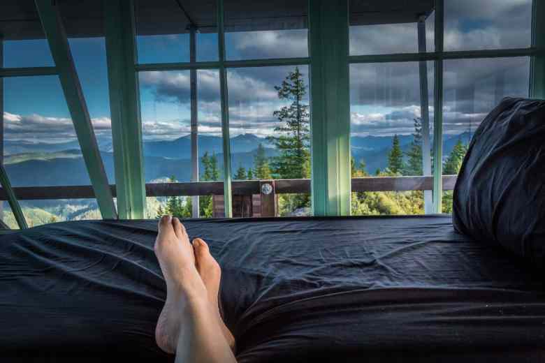 Feet propped up on the bed enjoying the view from inside Gold Butte Lookout Tower