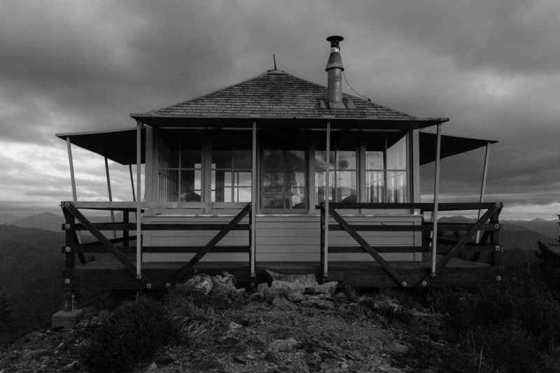 One Room Lookout Tower On Mountain Peak in black and white