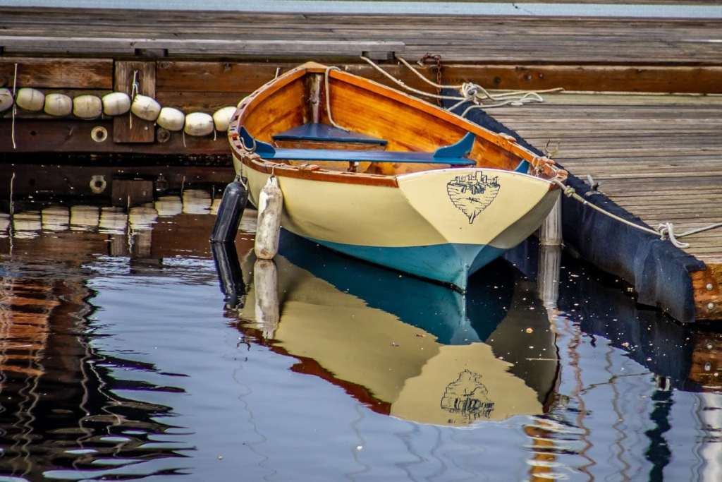 Small Wooden Row Boat Floating in a Dock