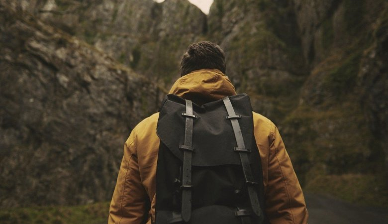 Man wearing a yellow rain jacket and black backpack