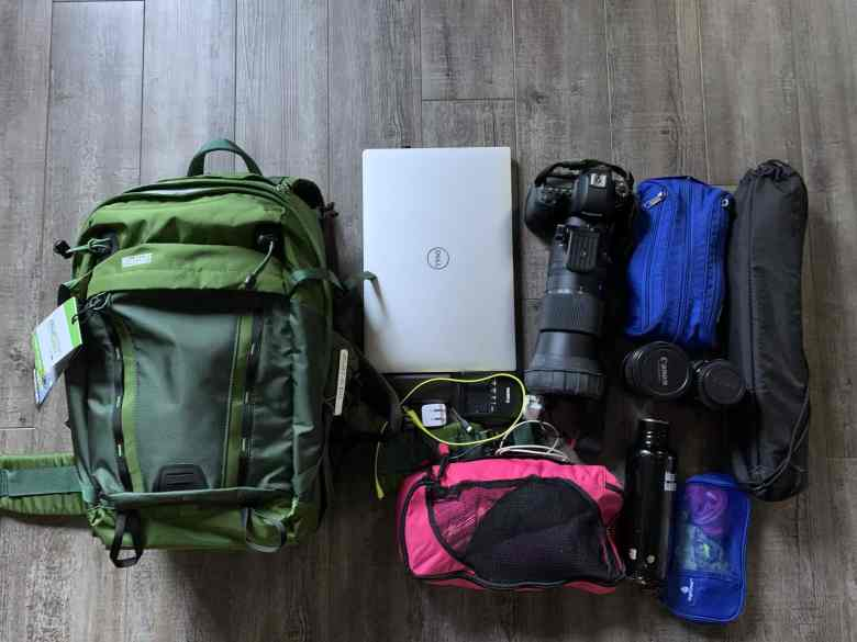 Flat Lay of green hiking camera Backpack with photography and travel equipment