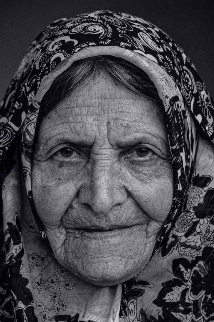 Black and white image of middle eastern woman in a floral hijab