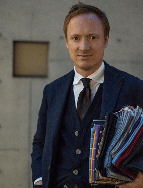 Michael Hill, Creative Director of Drake's, with a handful of bespoke tie cloth on his arm