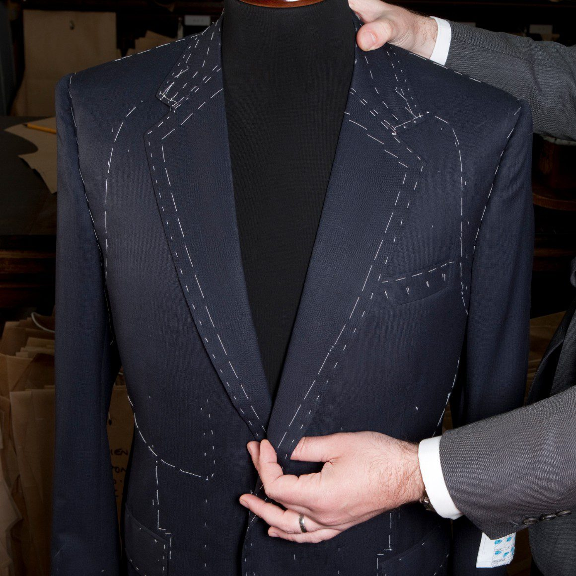 Tailor measuring for a bespoke suit