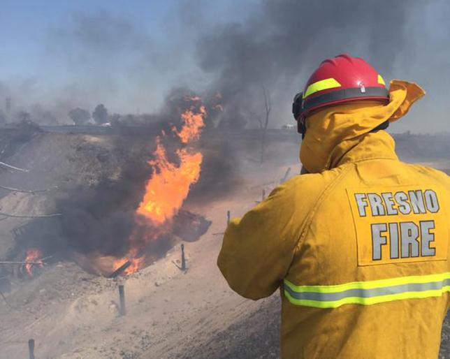 A firefighter watches the blaze after a gas line exploded near Fresno
