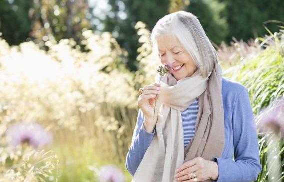 "alt=""Older woman smelling flowers outdoors"""