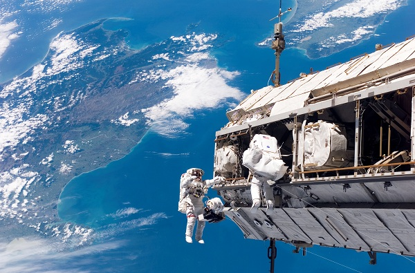 2 astronauts on a spacecraft in space