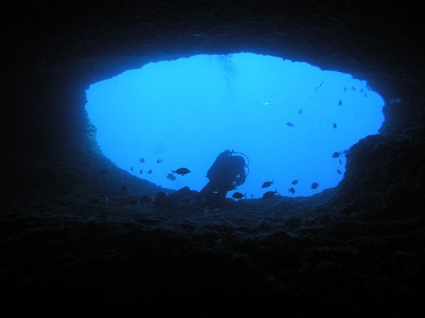 a man scuba diving into an underwater cave