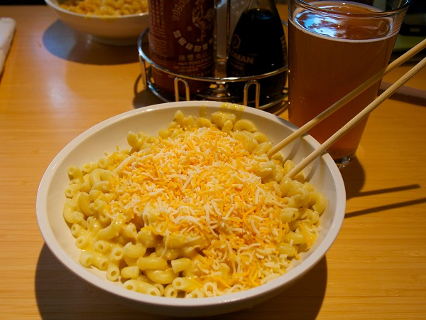 Mac and cheese on a restaurant table eaten with chopsticks