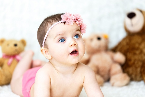 Beautiful baby girl among stuffed toys