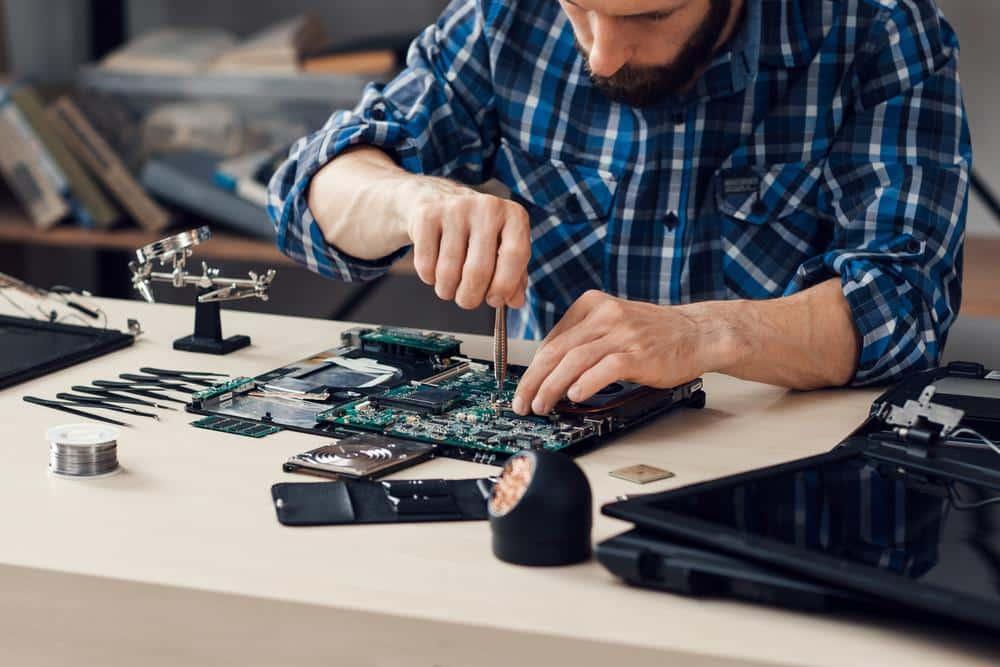 Technicien en train de réparer un ordinateur portable
