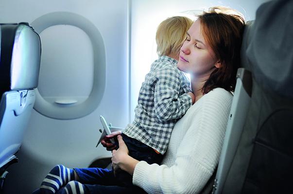 Flugangst - Frau mit Kind leidet an Angst im Flugzeug