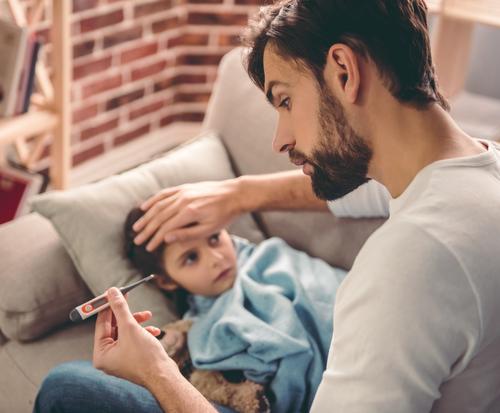 Vater misst bei seinem Sohn Fieber