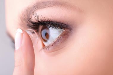 Frau gibt Kontaktlinse in Auge