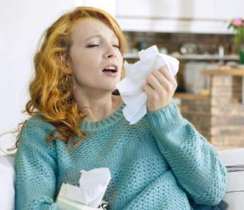Immunsystem - niesende Frau in Pullover auf Couch