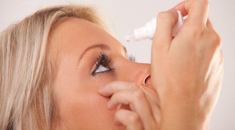 Frau tropft Augentropfen in Auge