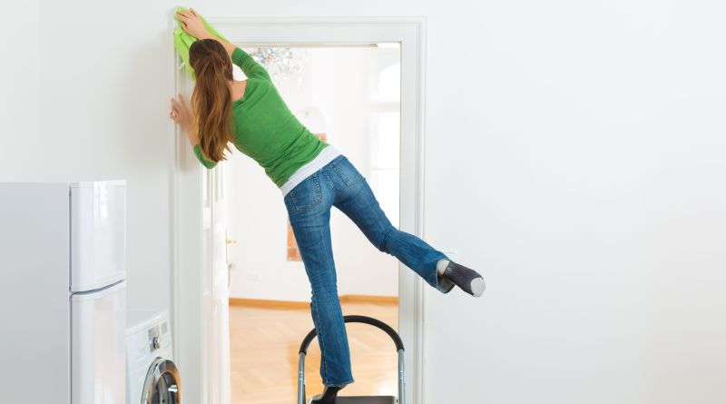 Frau putzt Türrahmen auf wackeligem Stuhl. Haushaltsverletzungen